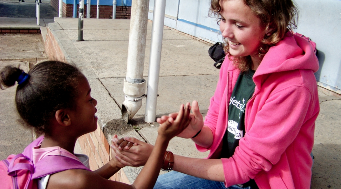 Childcare volunteer plays a game with a child during her volunteer work with children in South Africa